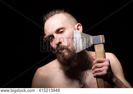 Young Handsome Man With Bushy Beard And Large Mustache Shaves His Beard With An Old Ax