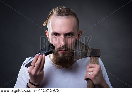 Young Handsome Bearded Man Shaves Bushy Beard With Trimmer And Ax