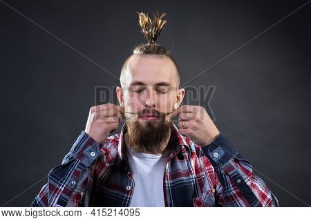 A Young Man With A Thick Beard And A Stylish Haircut Winds A Long Mustache