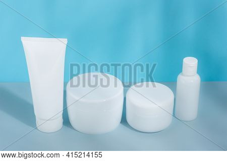 A Set Of Cosmetic Tubes For Cream, Different Sizes, Clean, White Without Inscriptions, On A Gray-blu