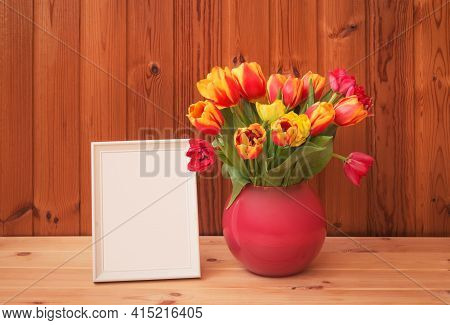 White Frame And Bouquet Of Fresh Tulips In Vase On Wooden Table. View With Copy Space.
