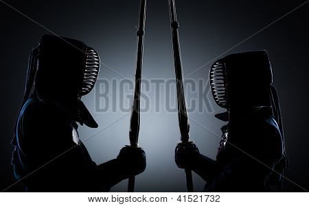 Two kendo fighters opposite each other with shinai. Japanese martial art of sword fighting
