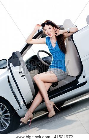 Pretty woman in sunglasses sits in the car with door opened