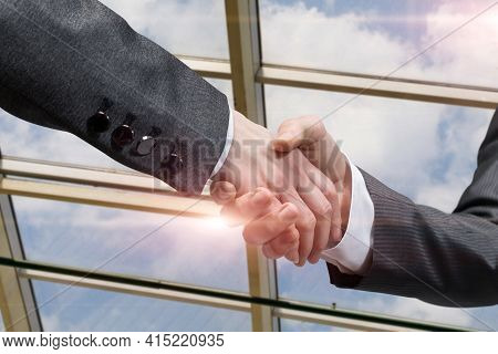 Shaking Hands As An Agreement In Business. Businessmen Shake Hands On The Background Of Panoramic Wi