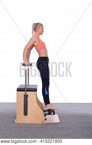 A 20-year-old Trainer Demonstrates How To Properly Practice Pilates On A Machine. She Stands On Her