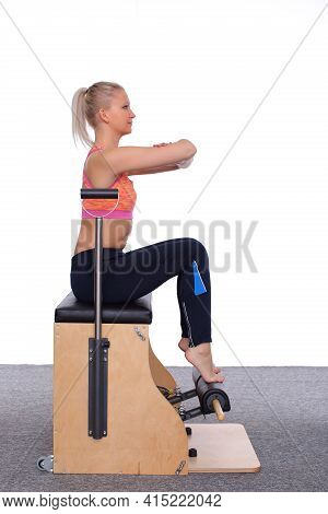 The 20-year-old Trainer Practices Pilates On An Elevator Chair, Sitting Up Straight With Her Arms Ra