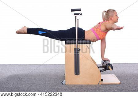 A 20-year-old Trainer Is Practicing Pilates On An Elevator Chair, Lying On Her Stomach Supporting He