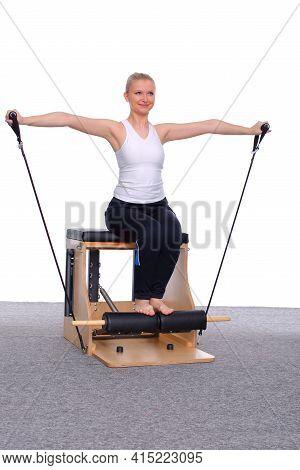 A 20-year-old Trainer Practices Pilates On An Elevator Chair With The Help Of A Gymnastics Rubber Ba