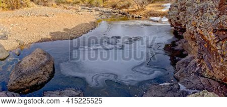 A Frozen Pond At The Base Of A Basalt Cliff In Devil Dog Canyon Near Drake Arizona.