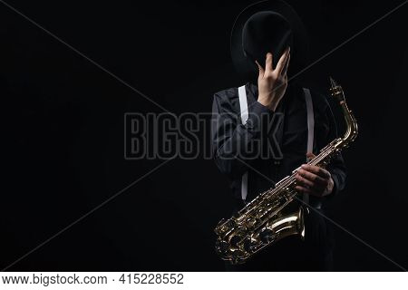 Male Musician Hiding Face With Trendy Hat While Posing In Studio With Saxophone In Hands. Concept Of