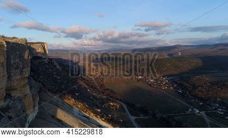 Top View Of Rocky Cliff On Background Horizon Of Mountains. Shot. Beautiful Landscape With Majestic