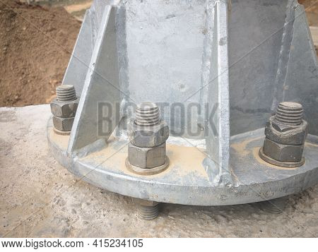 Close-up Of Anchor Bolts Fasten Metal Pillar To Concrete Foundation. Mantling Of Pillar With Anchor