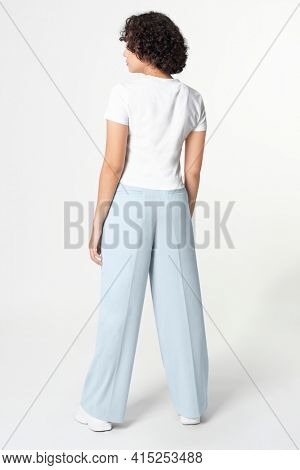 Woman in white tee and blue loose pants minimal fashion rear view