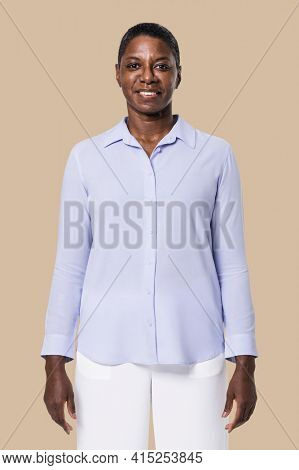 African American woman wearing blue long-sleeve shirt with white pants