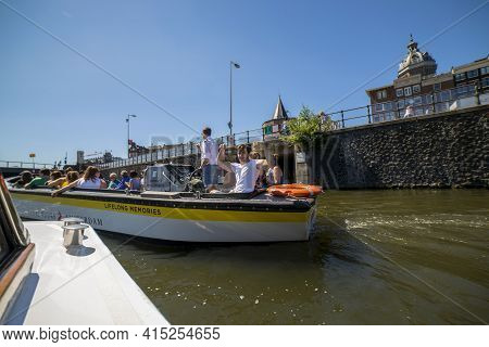 Amsterdam, Netherlands - July 02, 2018: People On A Pleasure Boat Sail Along The Amstel River In Ams