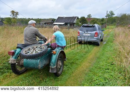 Russia - August 28, 2020. Tver Region, Russia. In The Village, A Car Pulls A Stalled Motorcycle On A