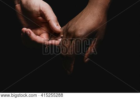 Multicultural people black and white holding hands photo closeup