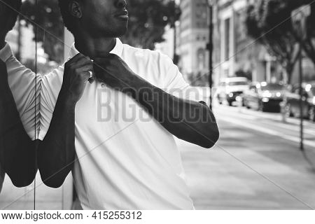 Black and white man buttoning polo shirt city portrait