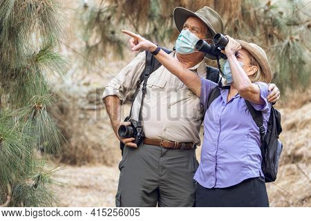 Couple appreciating the beauty of nature with binoculars during the new normal