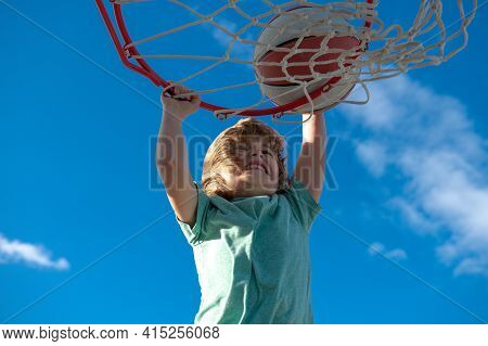 Kid Basketball Player Makes Slam Dunk. Active Kids Enjoying Outdoor Game With Basketball