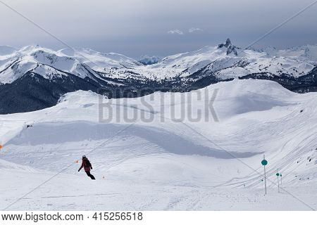 Snow Capped Mountain Vista Of Black Tusk And Skiers On Whistler, Bc.