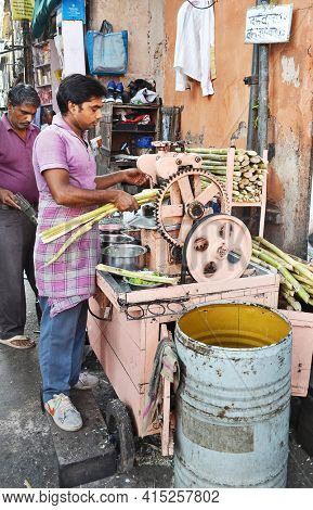 JAIPUR, INDIA - NOVEMBER 13, 2015: Squeezing sugar cane. Men extract the juice from sugar cane in an alley in Jaipur.