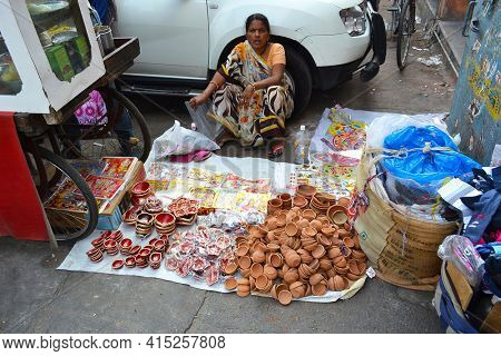 JAIPUR, INDIA - NOVEMBER 3, 2015: Street Vendor in Jaipur, with her wares spread out on the sidewalk.