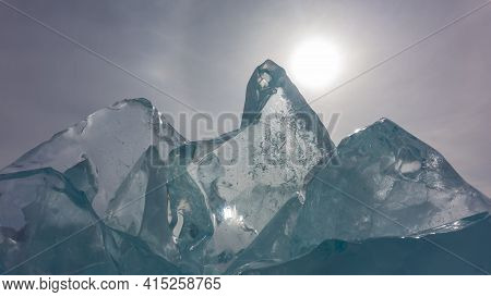 Large Transparent Turquoise Ice Floes Against The Sky. The Sun Is Peeping Out Over The Edge. A Bizar