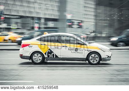 Moscow, Russia - January 2021: White City Taxi Yandex On The Wet Street. Sedan Taxi Cab Hyundai Sola