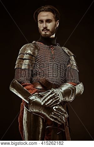 Portrait of medieval knight with sword and armour on a black background. Historical shoot.