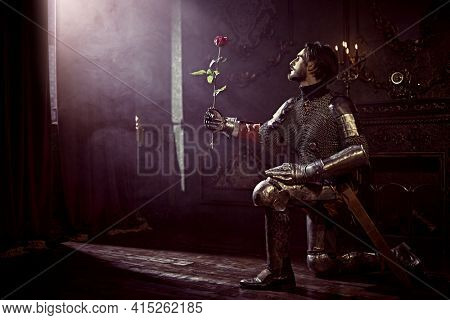 The noble knight in armor knelt down and holds out the rose in his hands looking at the light in the castle. Romance.