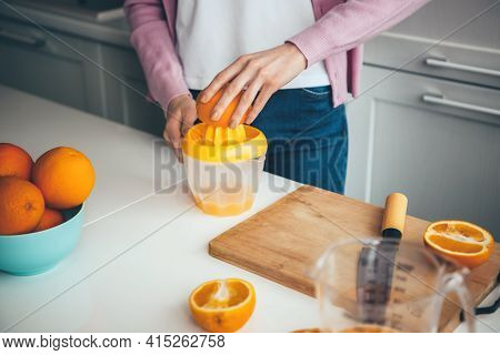 Caucasian Woman Is Squeezing Fresh Citrus Juice At Home Using A Manual Squeezer