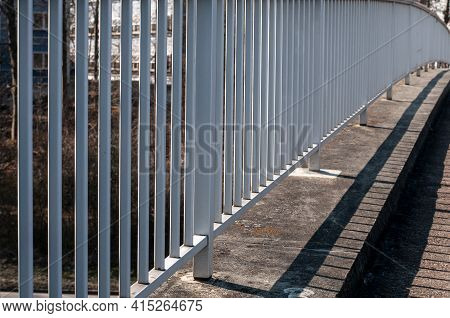 Diminishing Perspective Of A White Painted Metal Railing At A Footbridge On A Sunny Day