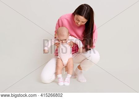 Young Dark Haired Beautiful Mother Wearing Casual Sweater And Pants With Infant Baby, Mommy Teaching