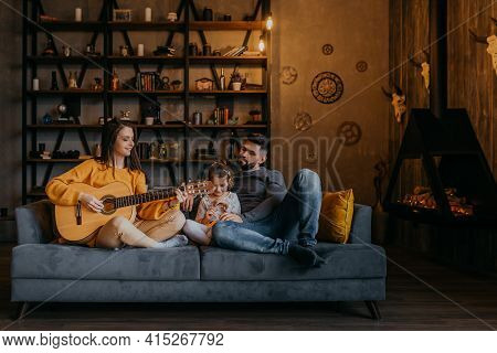 Young Woman Playing Guitar On Couch At Home. Woman In Orange Hat Sitting With Family On Sofa. Happy