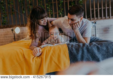 Family With Baby Laying In The Bed. Happy Mother And Father On The Bed With Kid In The Middle.