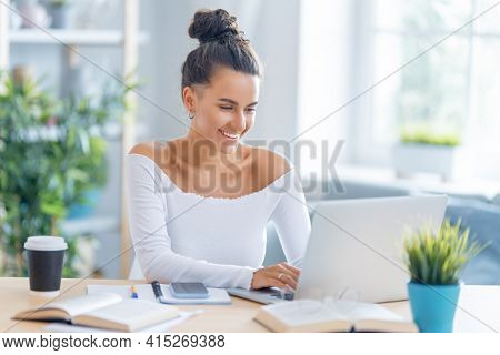 Happy casual beautiful woman working in home office.