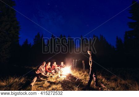 Friends Spend An Evening By Burning Fire At Campsite In Forest.