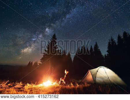 Girl Is Sitting By The Fire On Background Of Tent And Spruce Forest Under Starry Sky On Which Milky
