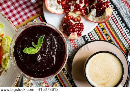 A Cup Of Coffee On A Table In A Coffe Shop In A Beige Mug . Coffee With Pomegranat, Tea, Restaurant,