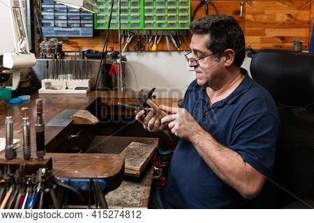 Foreground, Hammer Hammering A Silver Ring To Shape It In A Jewelry Workshop.