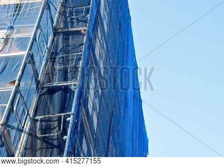 Repair Of The Facade Of The House. The Scaffolding Is Covered With A Blue Transparent Net Made Of Pl