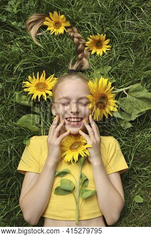 A Beautiful Girl With A Yellow Manicure Lies On The Grass With Sunflowers.
