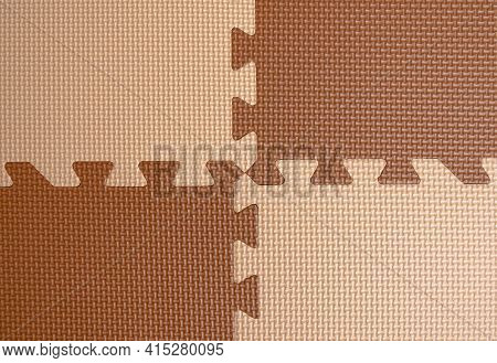 Four Pieces Of Foam Plastic Flooring In The Playroom. Beige And Brown Puzzle
