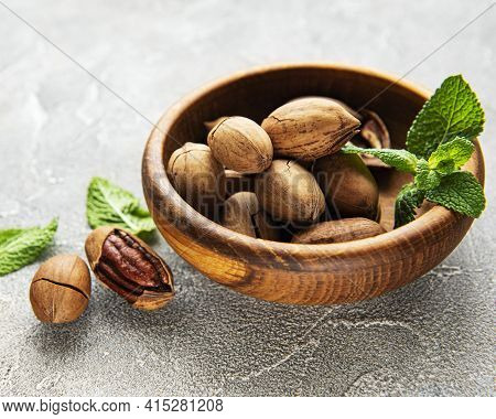Pecan Nuts In Bowl On A Grey Concrete Background