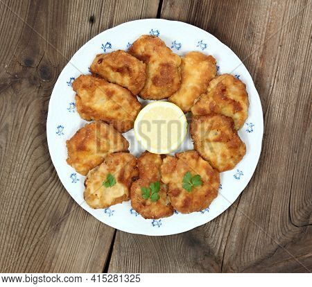 Pork Schnitzels Served On The Plate.  Decorated With Sliced Lemon And Parsley. Brown Rustic Table. T
