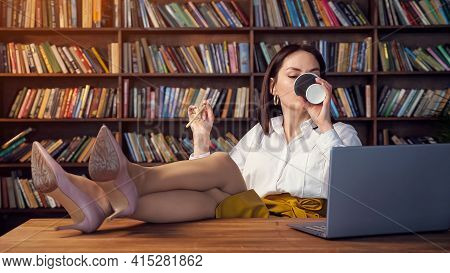 Sexy Businesswoman In White Blouse And Yellow Skirt Twirls Pencil Drinks Coffee And Types On Laptop