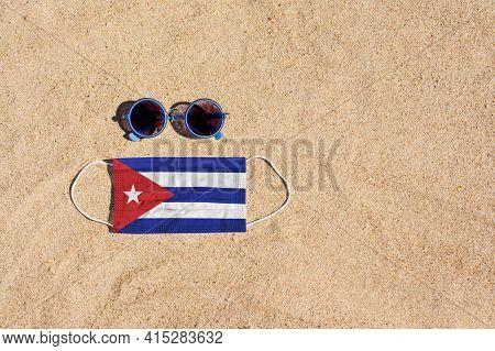 A Medical Mask In The Color Of The Cuba Flag Lies On The Sandy Beach Next To The Glasses. The Concep