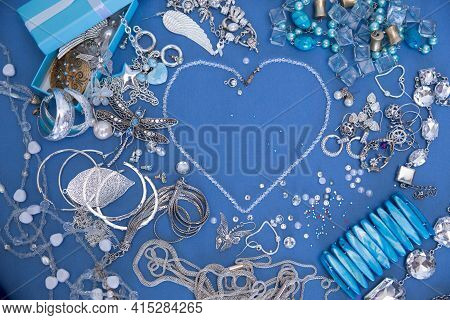 A Set Of Silver Jewelry. Space For The Text. Blue And Silver Jewelry On A Blue Background. Top View.