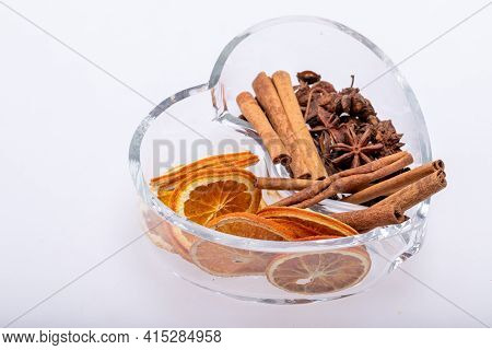Slices Of Dried Oranges, Cinnamon And Cardamom In A Heart-shaped Glass Dish